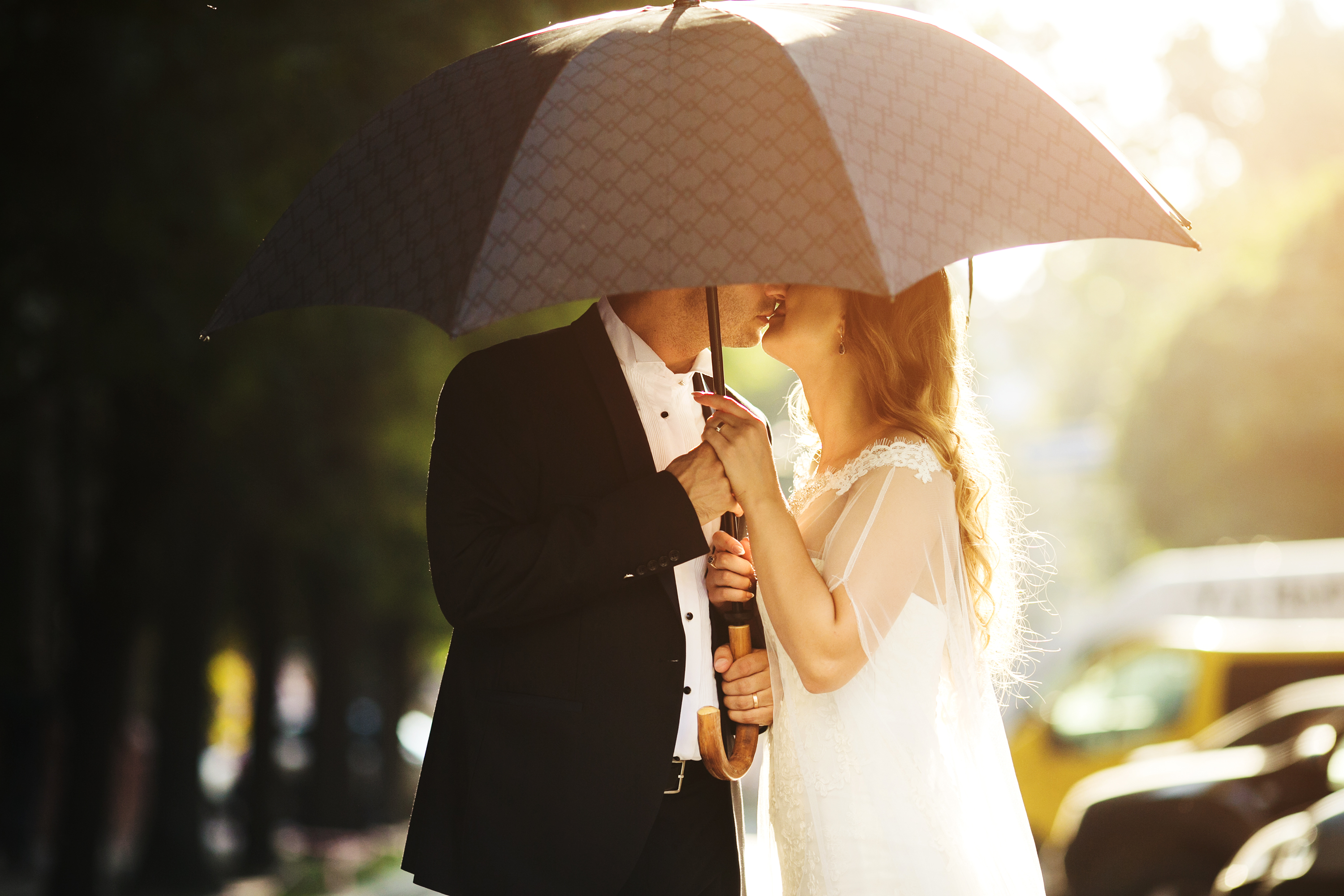 Wedding couple kissing on umbrella